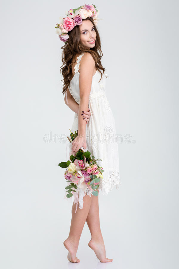 Beautiful woman in white dress and roses wreath standing barefoot stock image