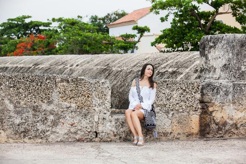 Beautiful woman on white dress sitting alone at the walls surrounding the colonial city of Cartagena de Indias. A Beautiful woman on white dress sitting alone at royalty free stock photos