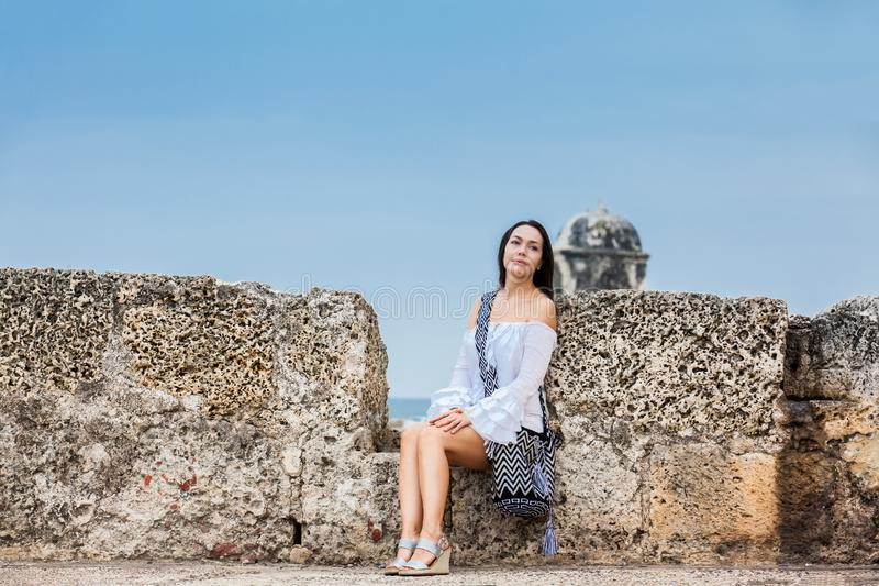 Beautiful woman on white dress sitting alone at the walls surrounding the colonial city of Cartagena de Indias. A Beautiful woman on white dress sitting alone at stock images