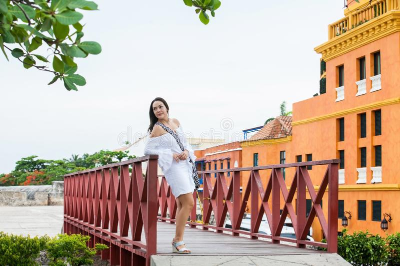 Beautiful woman on white dress standing alone at the walls surrounding of the colonial city of Cartagena de Indias royalty free stock image