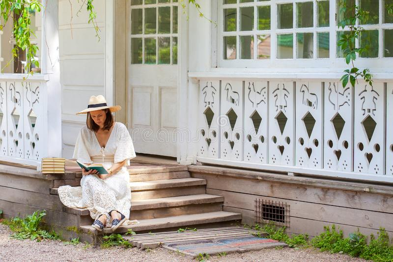 woman in a white dress and a straw hat reading a book on the porch of a rural house stock photo