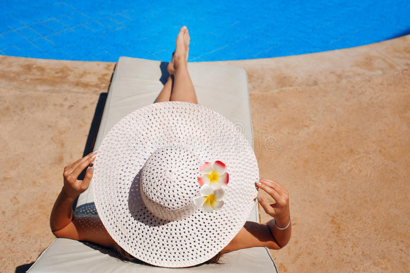 Beautiful woman in a white hat sunning by the pool. Beautiful woman in a big white hat sunning by the pool royalty free stock photos