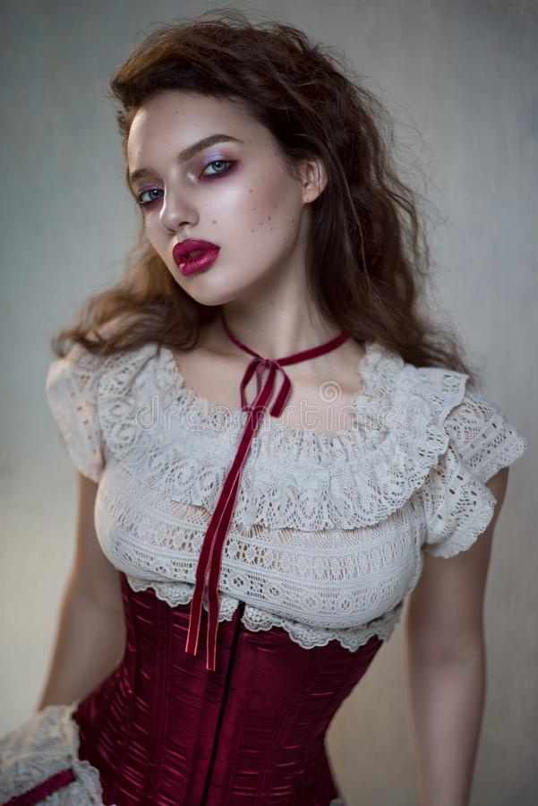 Beautiful woman in white lace and red corset royalty free stock images