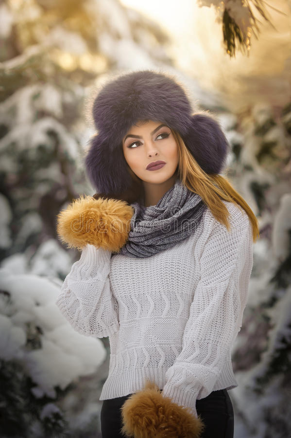 Beautiful woman in white pullover with over-sized fur cap enjoying the winter scenery in forest. Blonde girl posing in winter. Beautiful woman in white pullover stock photo