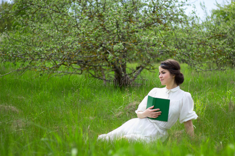 beautiful woman in white vintage dress with book on summer meadow royalty free stock image