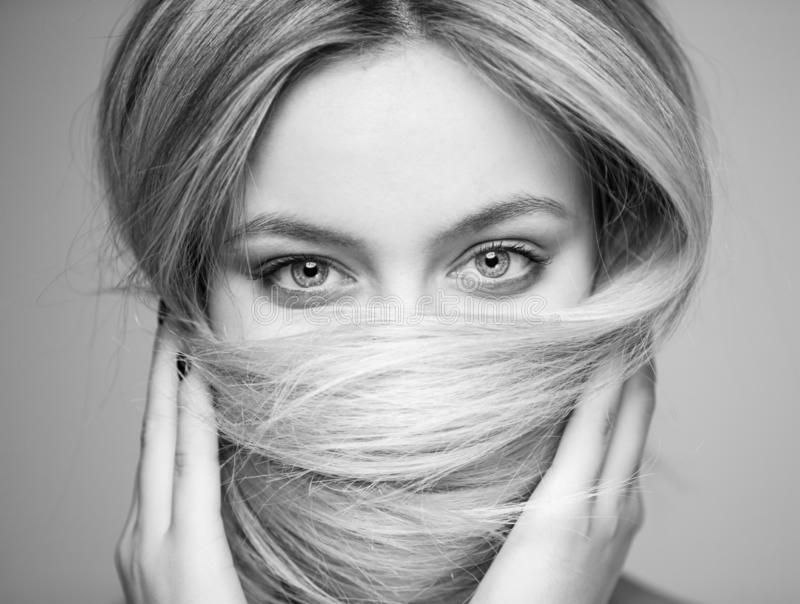 A beautiful woman who covered her mouth with hair, focus on the eyes. royalty free stock image