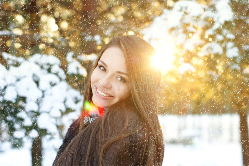 Beautiful woman in winter forest. Winter portrait of beautiful smiling woman with snowflakes in forest royalty free stock image