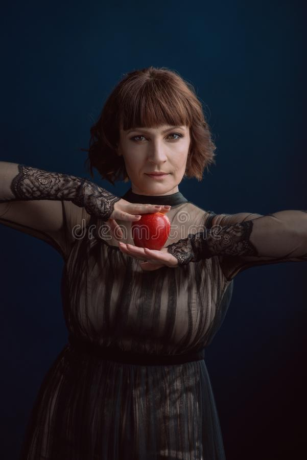 Beautiful woman witch with poison red apple stock image