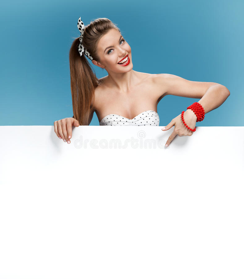 Beautiful woman woman put her hand on a blank white board, shows forefinger on the blank banner royalty free stock image