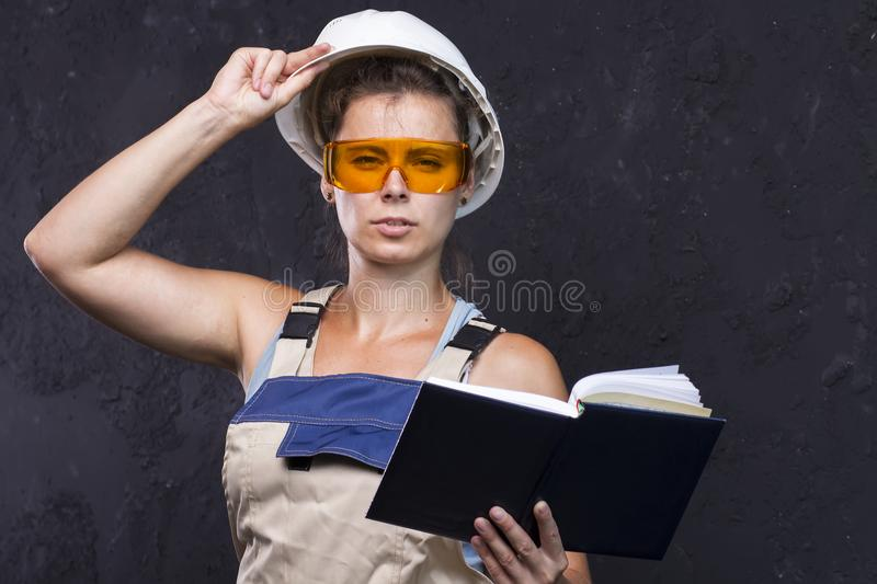 Beautiful woman worker builder in uniform with white helmet holds notebook. Portrait of cute young builder girl in work clothes. royalty free stock images