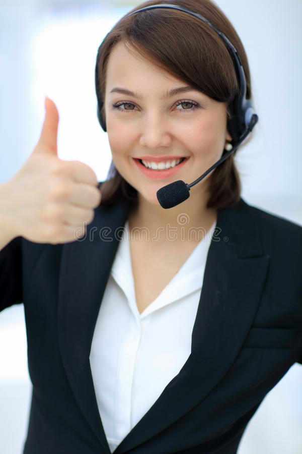 Beautiful woman working at callcenter, using headset showing thu. Smiling young woman working at callcenter, using headset showing thumb up royalty free stock image