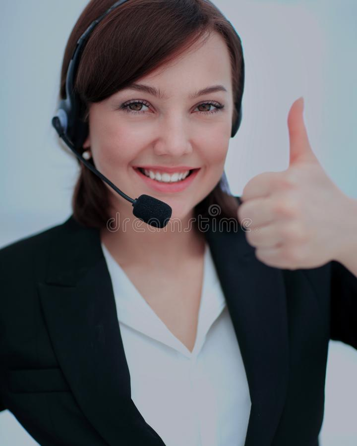 Beautiful woman working at callcenter, using headset showing thu. Smiling young woman working at callcenter, using headset showing thumb up royalty free stock photos