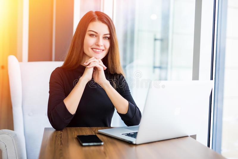 Beautiful woman working on her laptop on a stylish urban restaurant. Beautiful woman working on her laptop on a urban restaurant royalty free stock photo