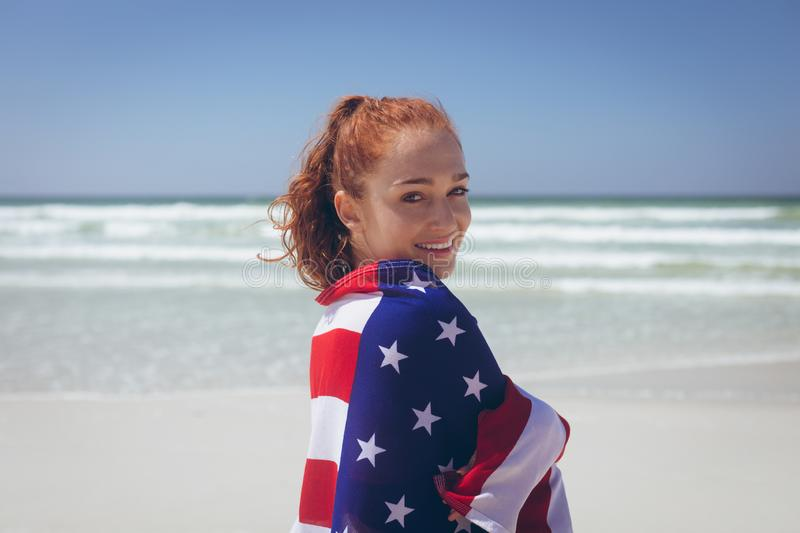 Beautiful woman wrapped in an american flag at beach stock photo