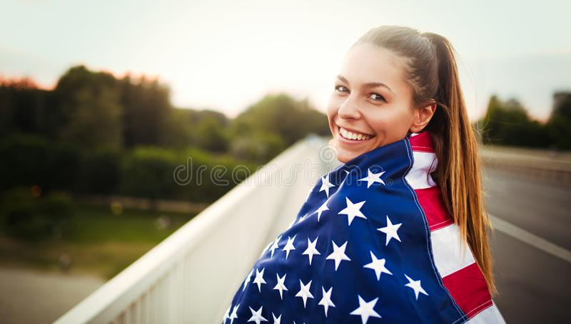 Beautiful woman wrapped in American flag. Beautiful young woman wrapped in American flag stock photo