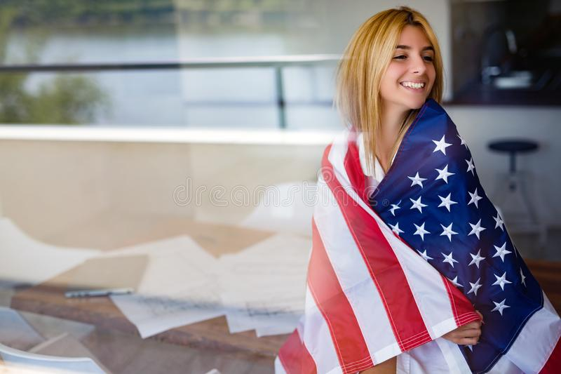 Beautiful woman wrapped in American flag. Beautiful young woman wrapped in American flag royalty free stock photos