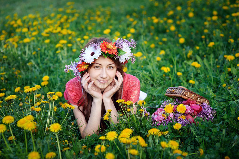 Beautiful woman in a wreath lying on the grass in a meadow.  royalty free stock images