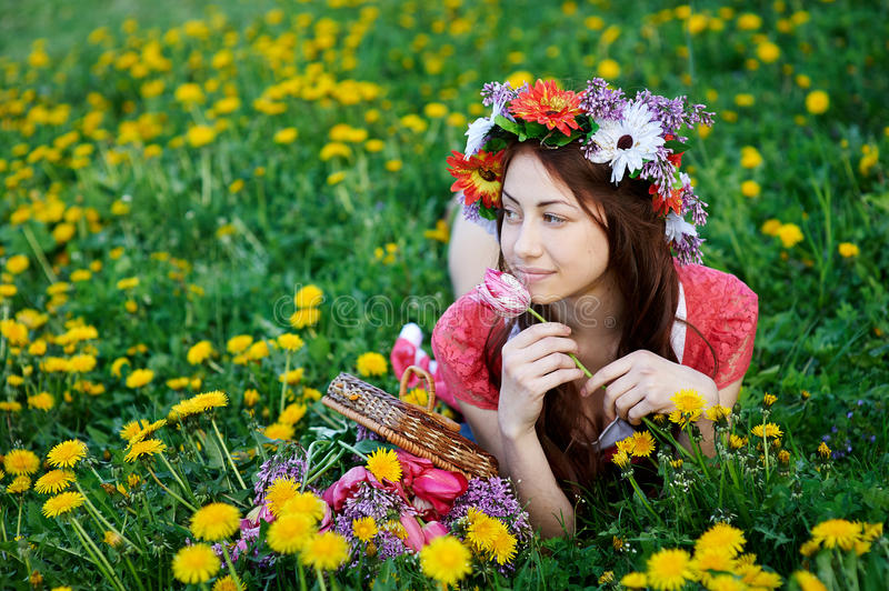 Beautiful woman in a wreath lying on the grass in a meadow stock photography