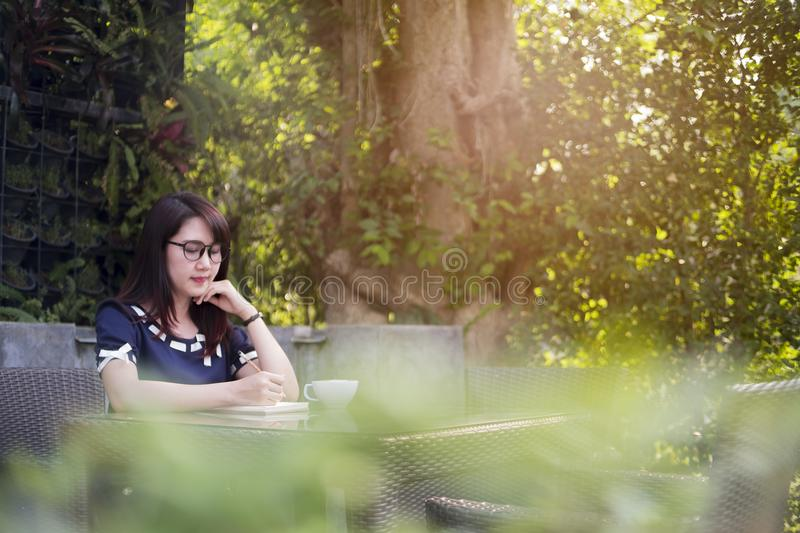 Beautiful woman writeing on book on teble, blurred background, b stock image