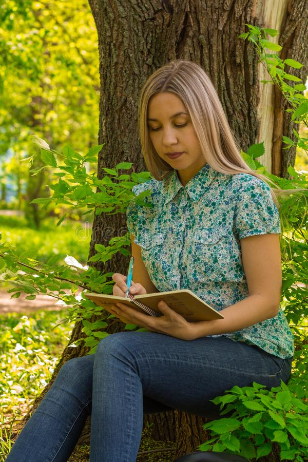 Beautiful woman writing in her diary in the park royalty free stock photo