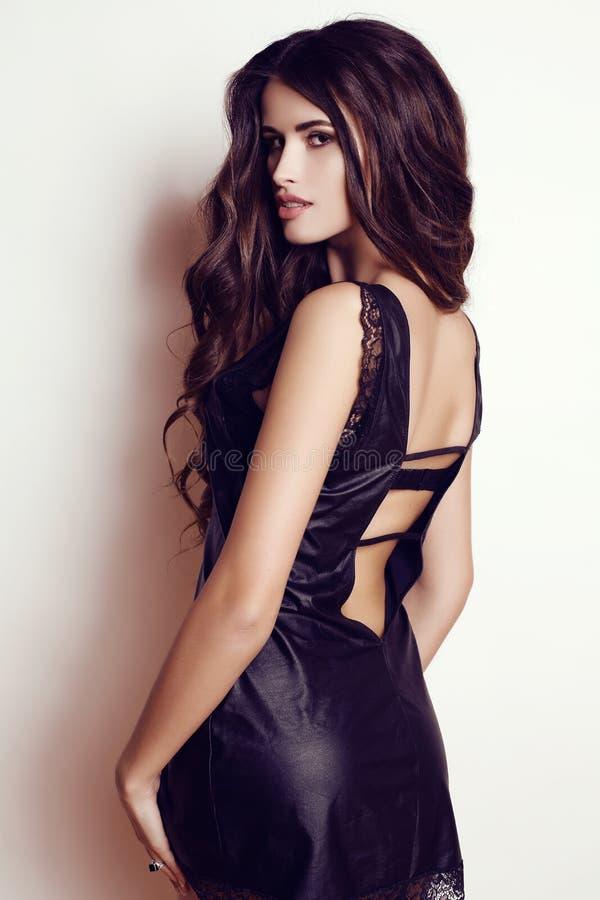 Beautiful woman wtih luxurious dark hair in elegant black dress stock photos