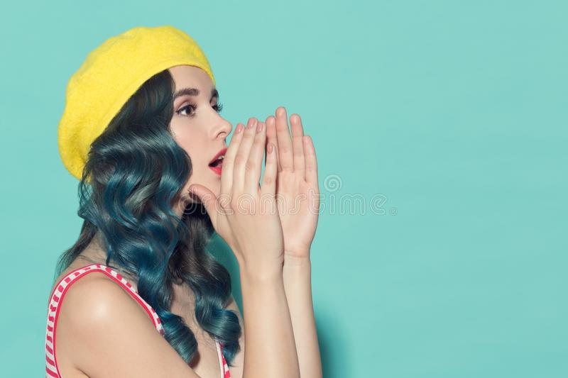 Beautiful woman in a yellow beret makes speaker from her hands. stock image