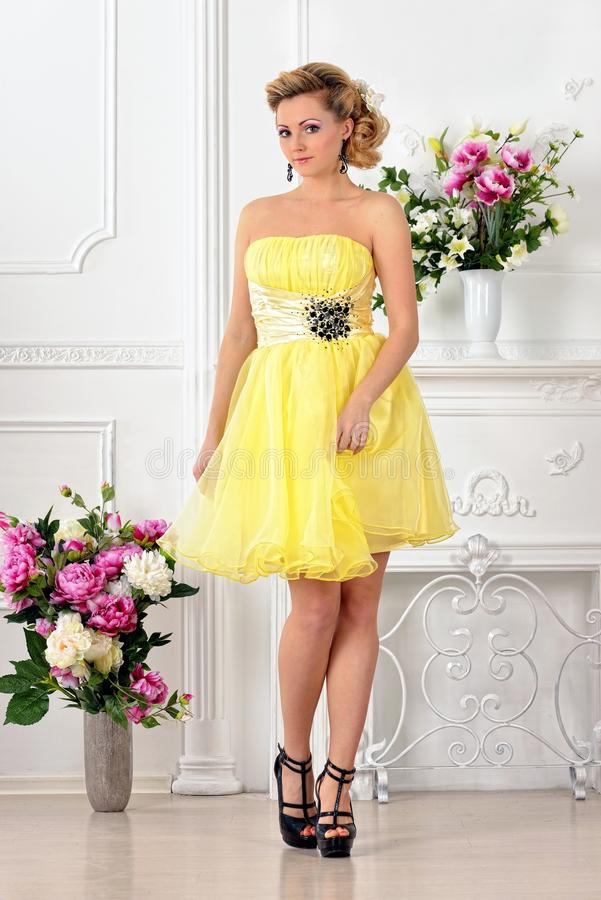 Beautiful woman in yellow dress in luxury studio. stock photography