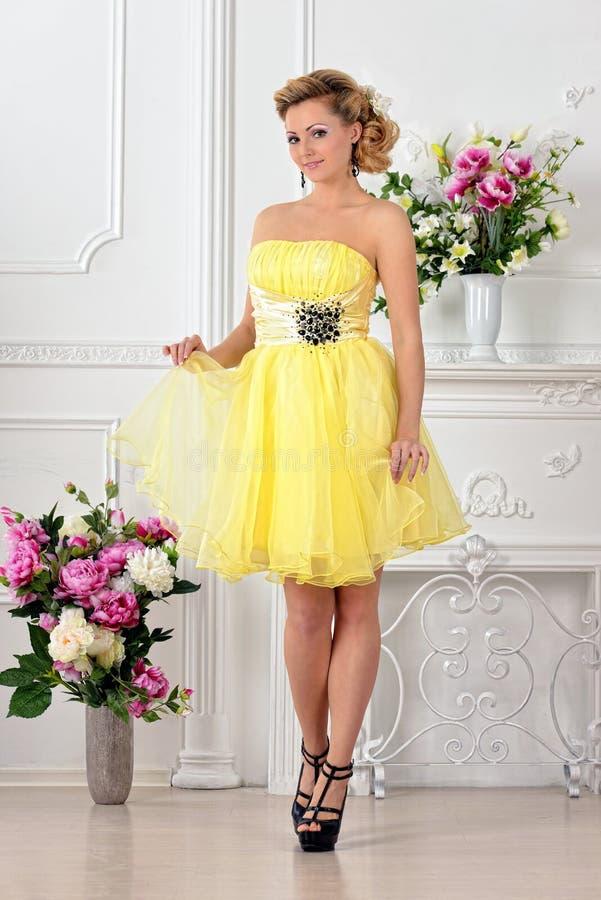 Beautiful woman in yellow dress in luxury studio. royalty free stock photo