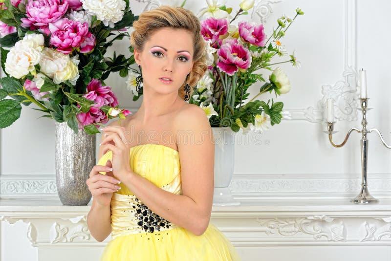 Beautiful woman in yellow dress in luxury studio. stock image