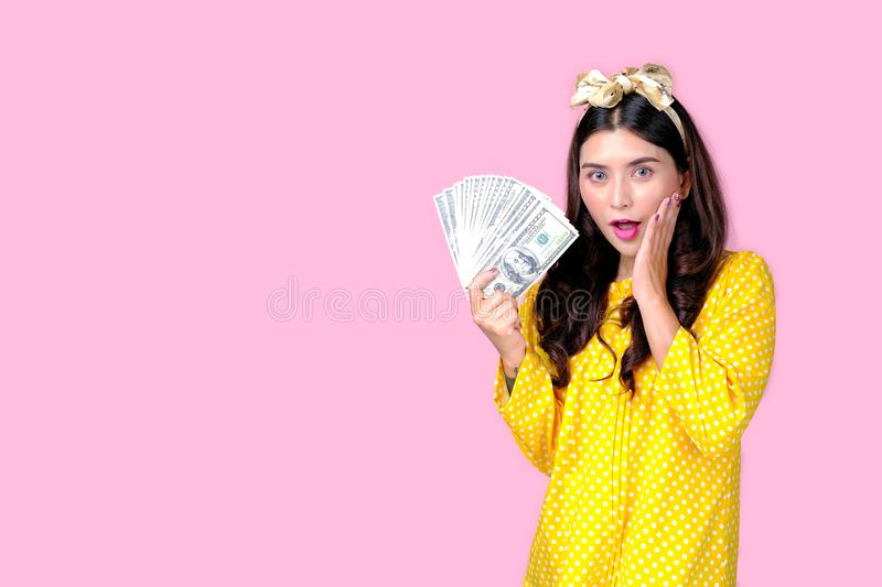 Beautiful woman with yellow headband and yellow dress hold the dollar banknote in front of pink background, also with concept of. Retro image and business stock image