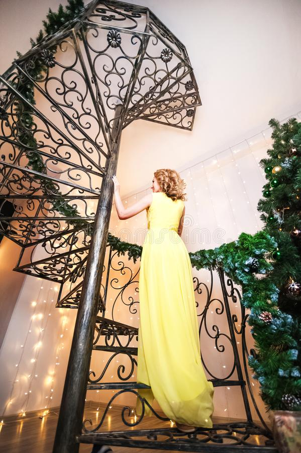 A beautiful woman in a yellow long dress is standing on a spiral staircase back. A girl dreams in a decorated living room for Chri royalty free stock images