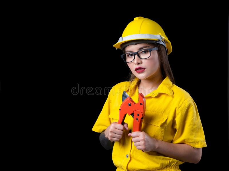 A beautiful woman in the yellow technician uniform holding a construction tool. In a studio with a black background, adult, asian, attractive, beauty, builder stock photo