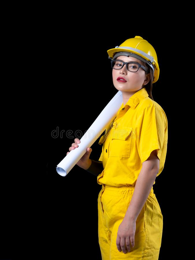 A beautiful woman in the yellow technician uniform holds a blueprint used in the construction. Of a studio with a black background, adult, asian, attractive stock image
