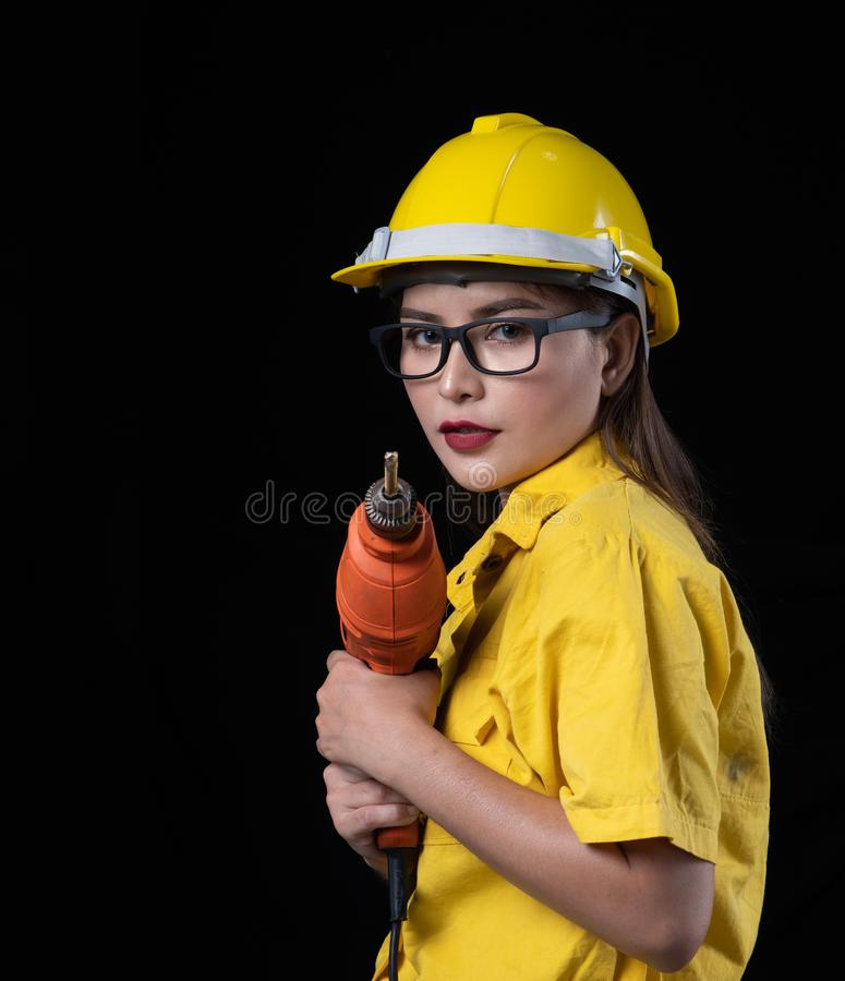 A beautiful woman in the yellow technician uniform holds a drill used in the construction. Of a studio with a black background, adult, asian, beauty, builder stock photography