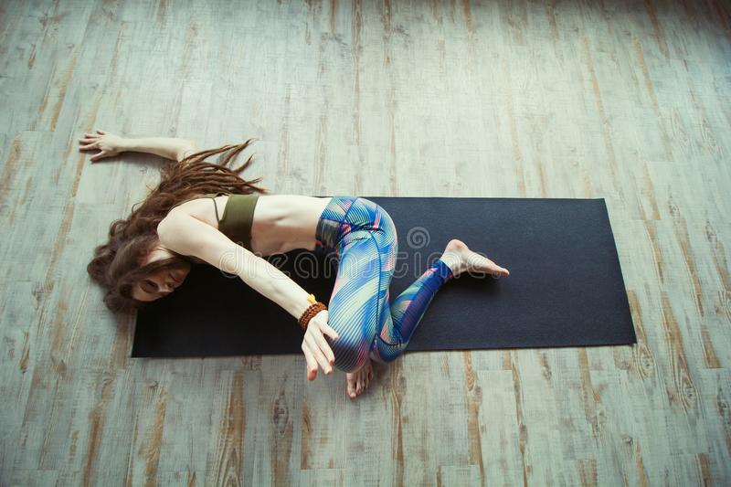 Beautiful woman in yoga class. Beautiful caucasian woman with long hair and slender body doing yoga on a mat top view stock images