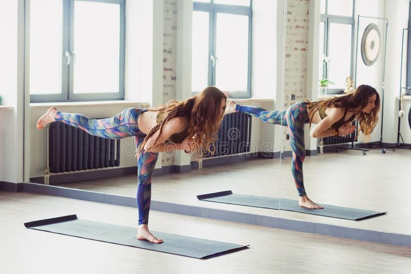 Beautiful woman in yoga class. Beautiful caucasian woman with long hair and slender body doing yoga in yoga class stock photography