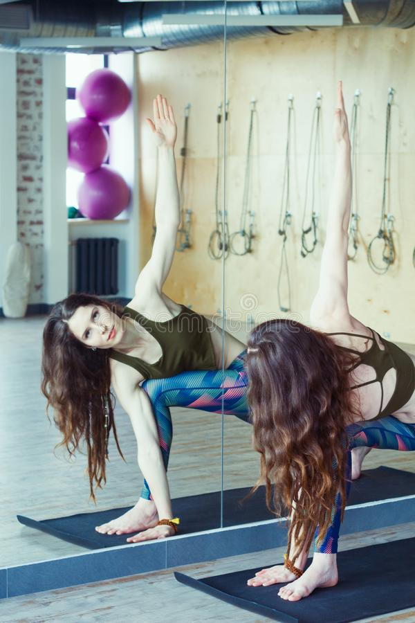 Beautiful woman in yoga class. Beautiful caucasian woman with long hair and slender body doing yoga in royalty free stock photos