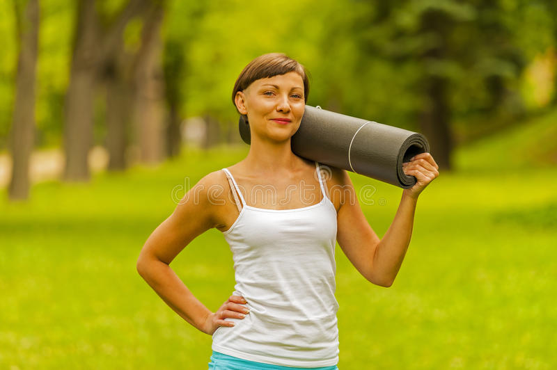 Beautiful woman with a yoga mat outdoors, in park. royalty free stock photography