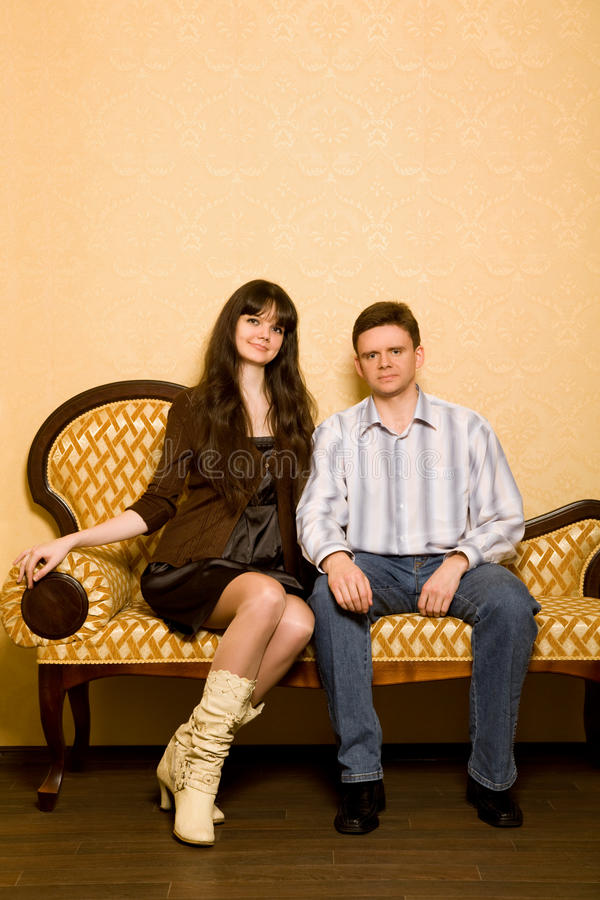 Beautiful Woman And Young Man Sitting On Sofa Royalty Free Stock Images