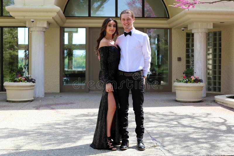 Beautiful woman in back prom dress and handsome guy in suit, teenager ready for a luxury night. stock images