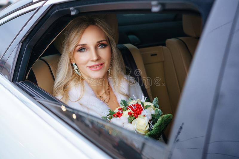 Beautiful woman bride with a bouquet of flowers and a man sitting in the car, looking out the window royalty free stock images