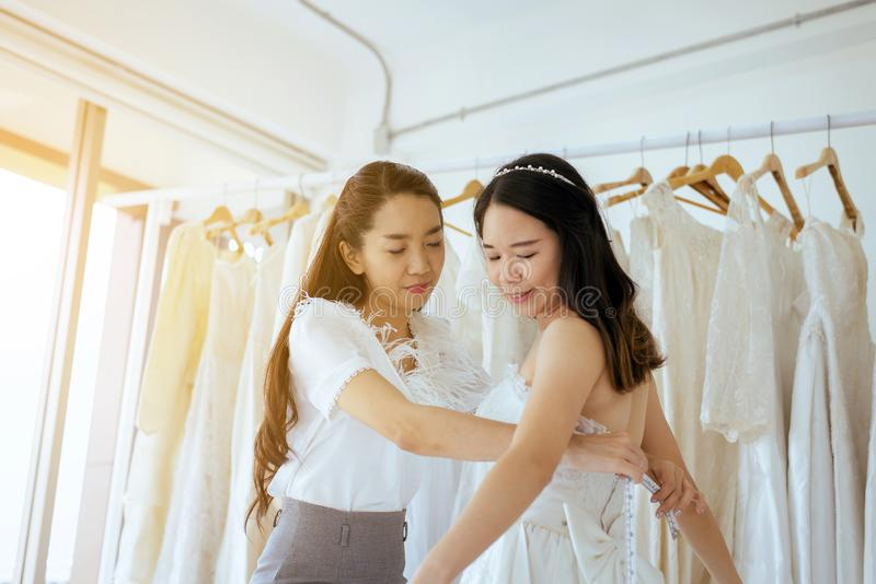 Beautiful woman bride trying on wedding dress,Asian women tailor making adjustment with measuring tape length of dress royalty free stock photo