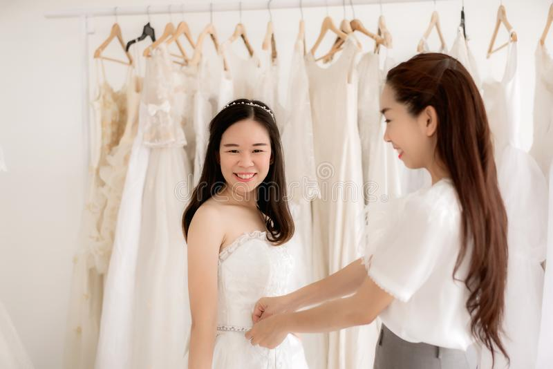 Beautiful woman bride trying on white wedding dress,Asian women tailor making adjustment on her client during fitting,Happy and sm royalty free stock images