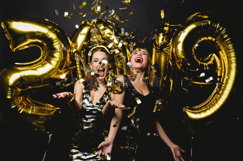 Beautiful Women Celebrating New Year. Happy Gorgeous Girls In Stylish Party Dresses Holding Gold 2019 Balloons. Having Fun At New Year`s Eve Party. Holiday stock image