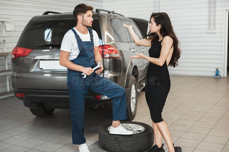 Beautiful woman client is complaining about bad service provided by mechanic in car damage department looking angry. Beautiful women client is complaining about stock photography