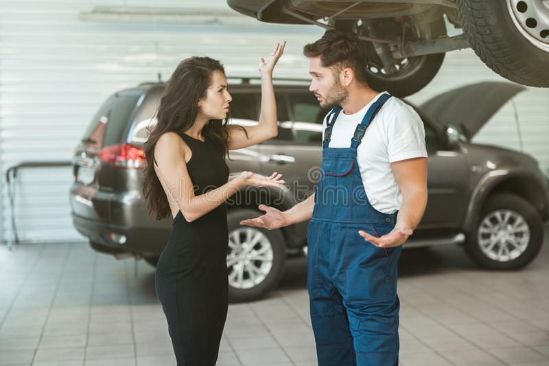 Beautiful woman client is complaining about bad service provided by mechanic in car damage department. Beautiful women client is complaining about bad service stock images