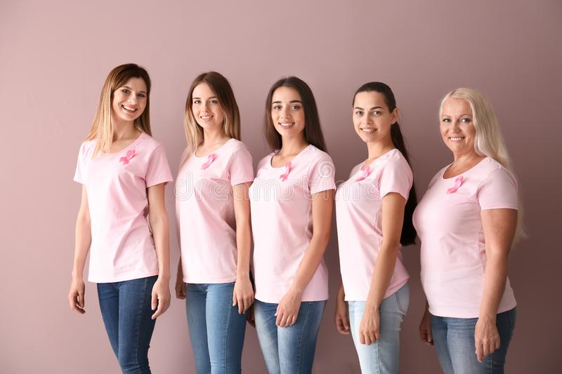 Beautiful women of different ages with pink ribbons on color background. Breast cancer concept royalty free stock image