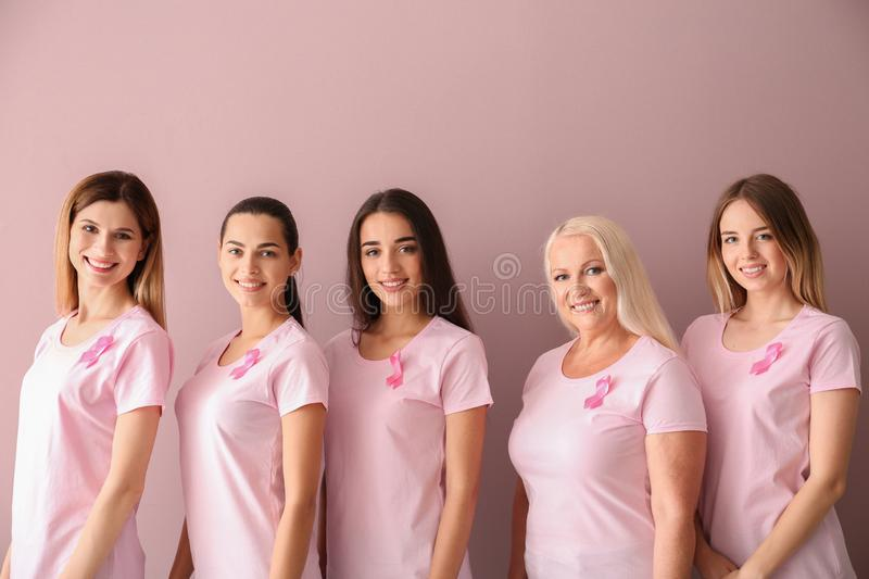 Beautiful women of different ages with pink ribbons on color background. Breast cancer concept stock image
