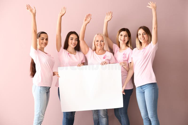 Beautiful women of different ages with pink ribbons holding poster on color background. Breast cancer concept stock images