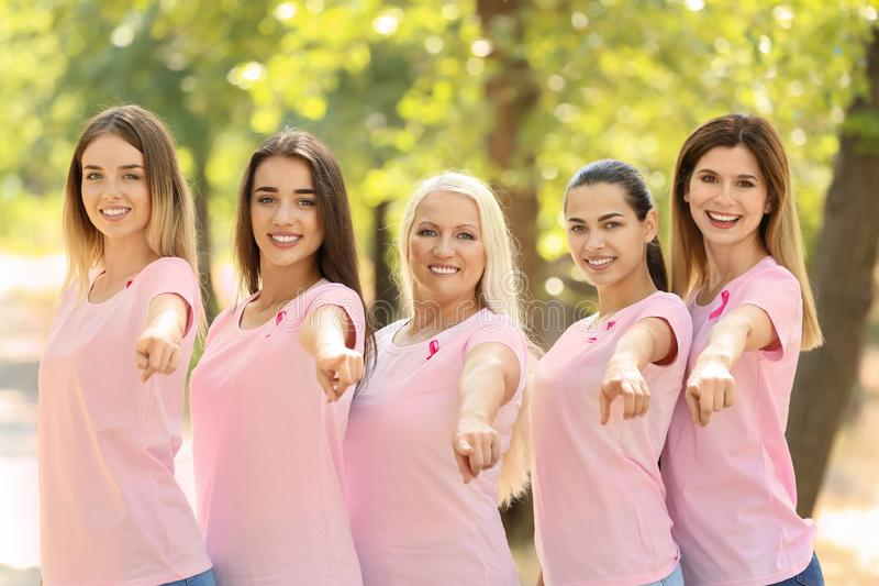 Beautiful women of different ages with pink ribbons outdoors. Breast cancer concept stock image